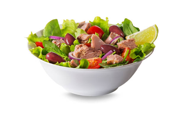 Tuna salad with lettuce, tomatoes and olives Tuna salad with lettuce, tomatoes and olives isolated on white background tuna animal stock pictures, royalty-free photos & images