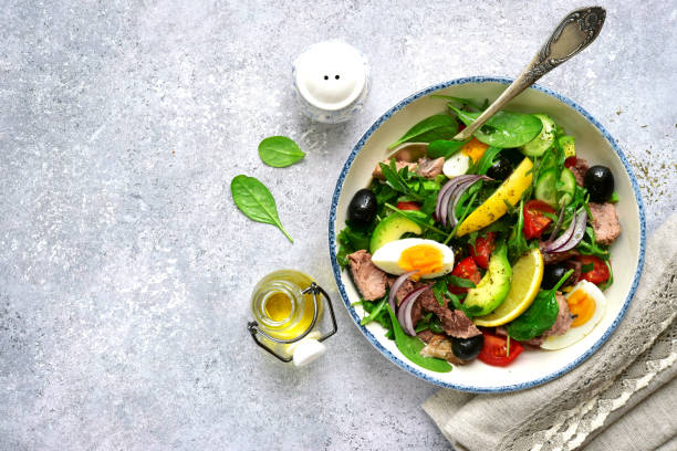 Tuna salad with mix salad leaves (spinach and arugula) , avocado, cherry tomato, cucumber and egg stock photo