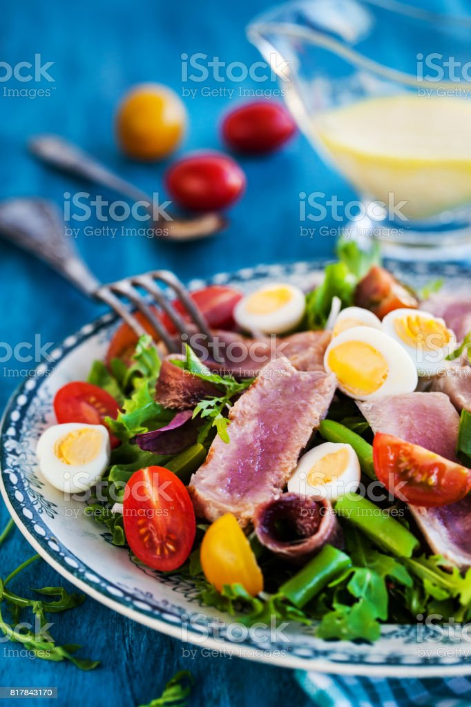 Tuna salad ( Nicoise) with tomatoes, boiled eggs, onion, anchovy and lettuce stock photo