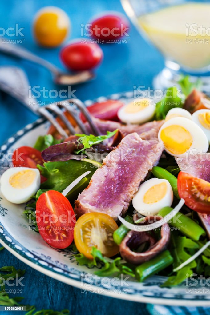 Tuna salad with tomatoes, boiled eggs, onion, anchovy and lettuce stock photo