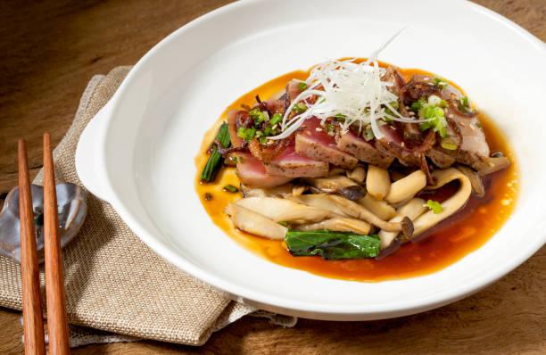 bife de atum em um prato branco é colocado sobre uma mesa de madeira, comida japonesa - fine dining - fotografias e filmes do acervo