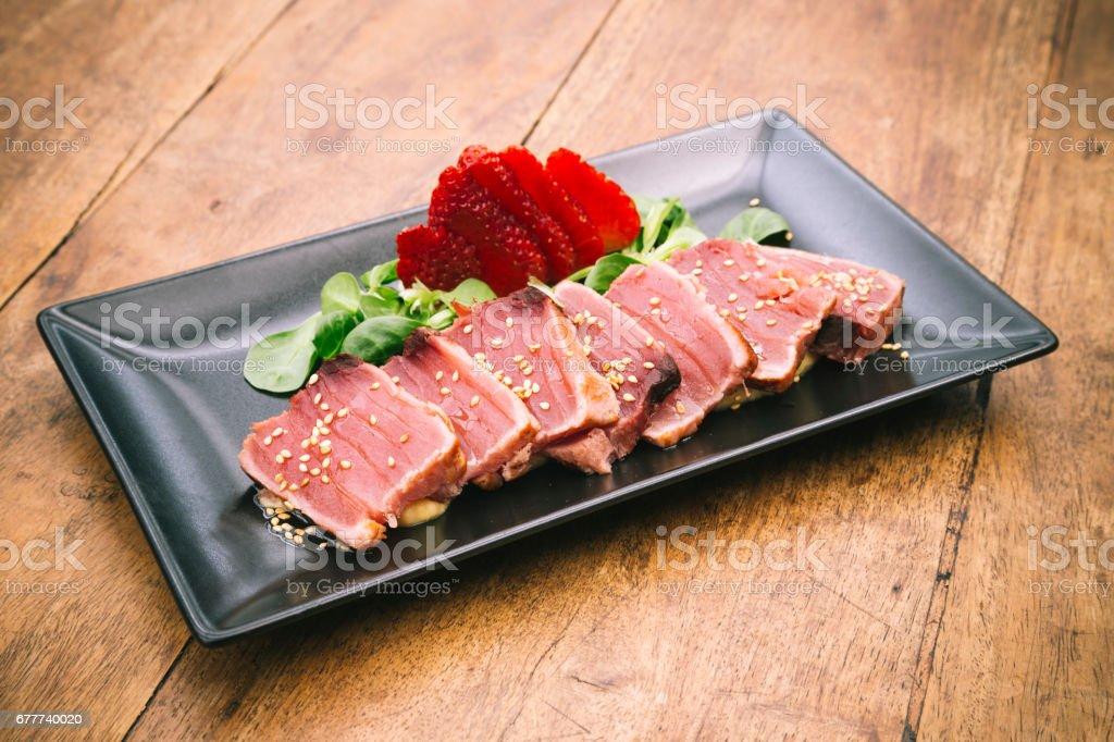 Tuna tataki dish on rustic wooden table stock photo