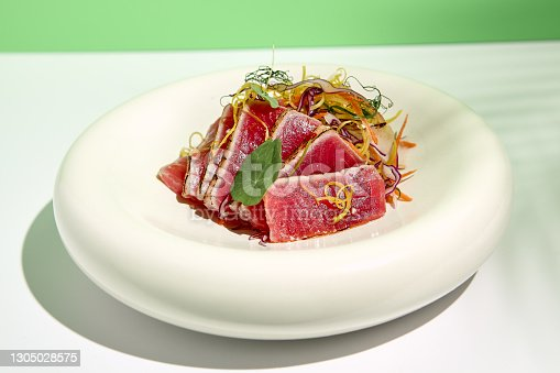 istock Tuna tataki in sesame with salad. Fish sashimi restaurant appetizer on white table with green wall. Day sunlight with hard shadow of tropical palm leaves. Summer or spring food concept. 1305028575