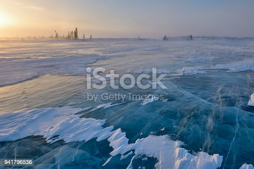 Frozen lake with boreal forest (taiga) and tundra in background at Wapusk national park, Canada, during blizzard.