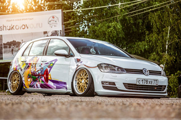Tuned by low suspension and custom wide golden colored wheels. White volkswagen golf 7 with aerography on which painted Chip and Dale characters. stock photo