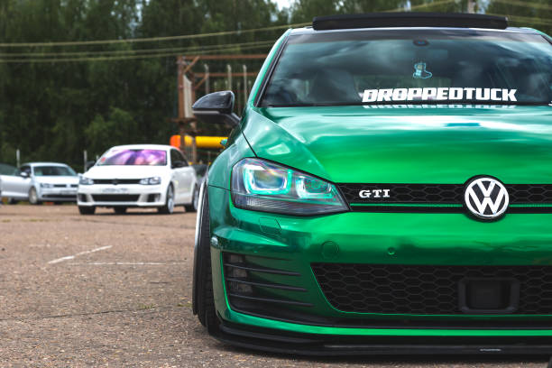 Tuned Volkswagen Golf 7 tightened into a green vinyl film. Installed exclusive wheels, air suspension. Lowrider in the parking lot. front view stock photo