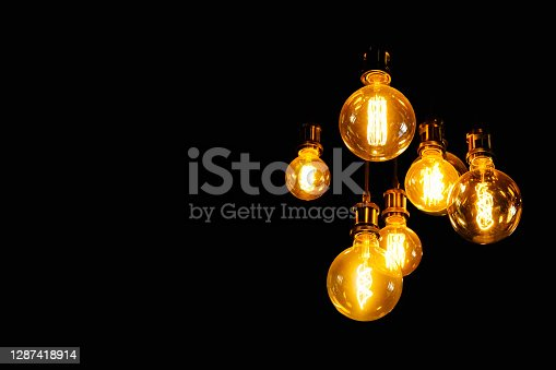 Tungsten lamp with black background for copy space. Old fashioned chandelier