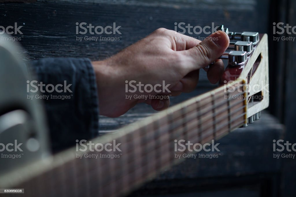 tuning an acoustic guitar on dark background stock photo