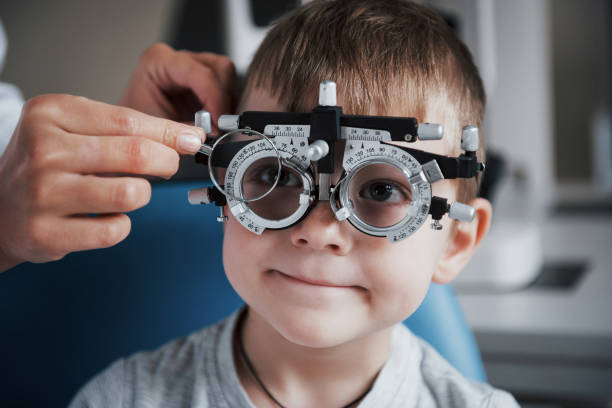 Tuning the intrument. Little boy with phoropter having testing his eyes in the doctor's office Tuning the intrument. Little boy with phoropter having testing his eyes in the doctor's office. optical instrument stock pictures, royalty-free photos & images