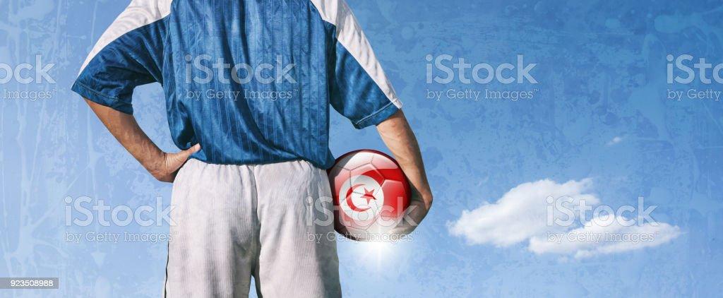Tunisia soccer player holding ball with tunisian flag stock photo