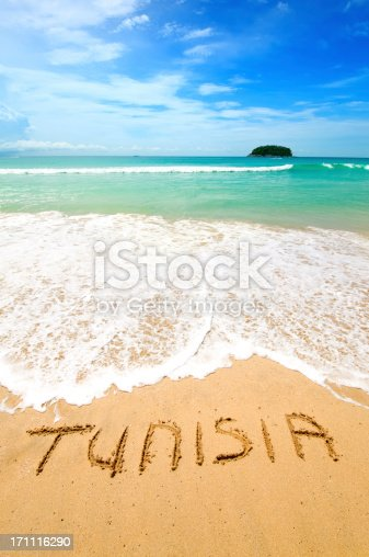 Tunisia written on the sand of a beautiful tropical beach. Visible are one island in the sea, turquoise water, little splashy waves, golden sand and beautiful cloudscape over the sea.See more images like this in: