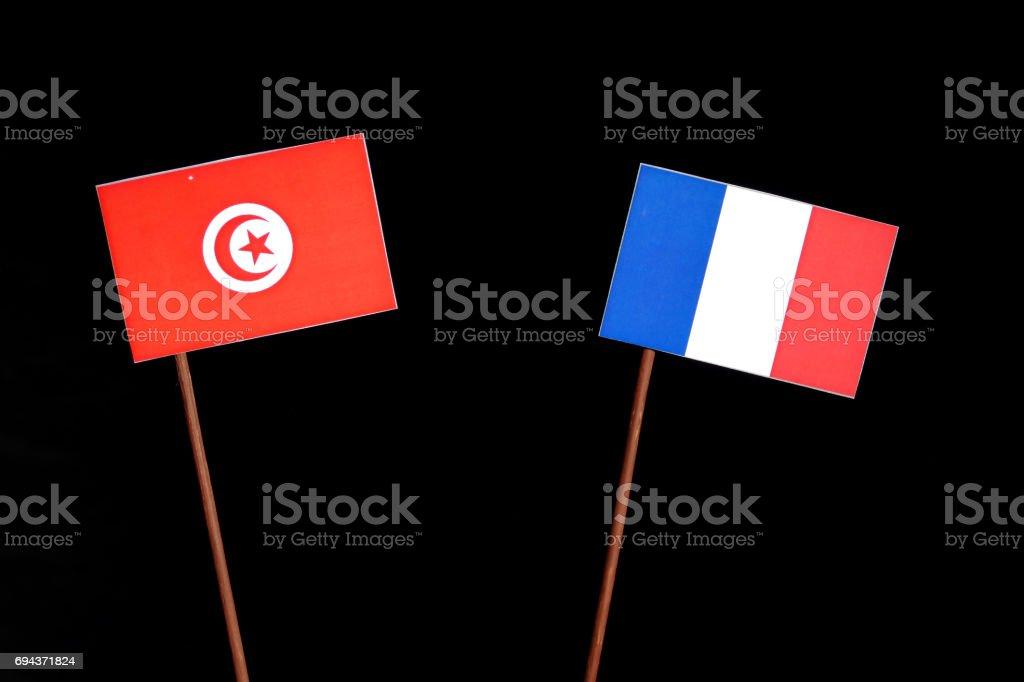 Tunisian flag with French flag isolated on black background stock photo