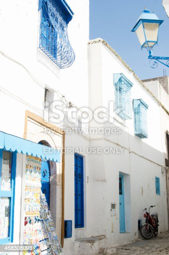 Sidi Bou Said, Tunisia- August 9, 2011: Small street in Sidi Bou Said with traditional white wall and blue gate and doorIn front small souvenir shop