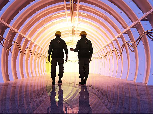 Tunnel Silhouette of workers in the tunnels. power occupation stock pictures, royalty-free photos & images