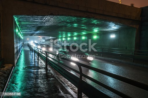 Pedestrian walkway and highway in a tunnel under the Stone bridge in a thick fog at night