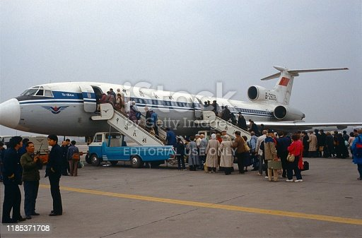 China (exact location unfortunately not known), 1985. Passengers board a Tupolev-150 over two gangways on an airfield. Also: Ground staff.