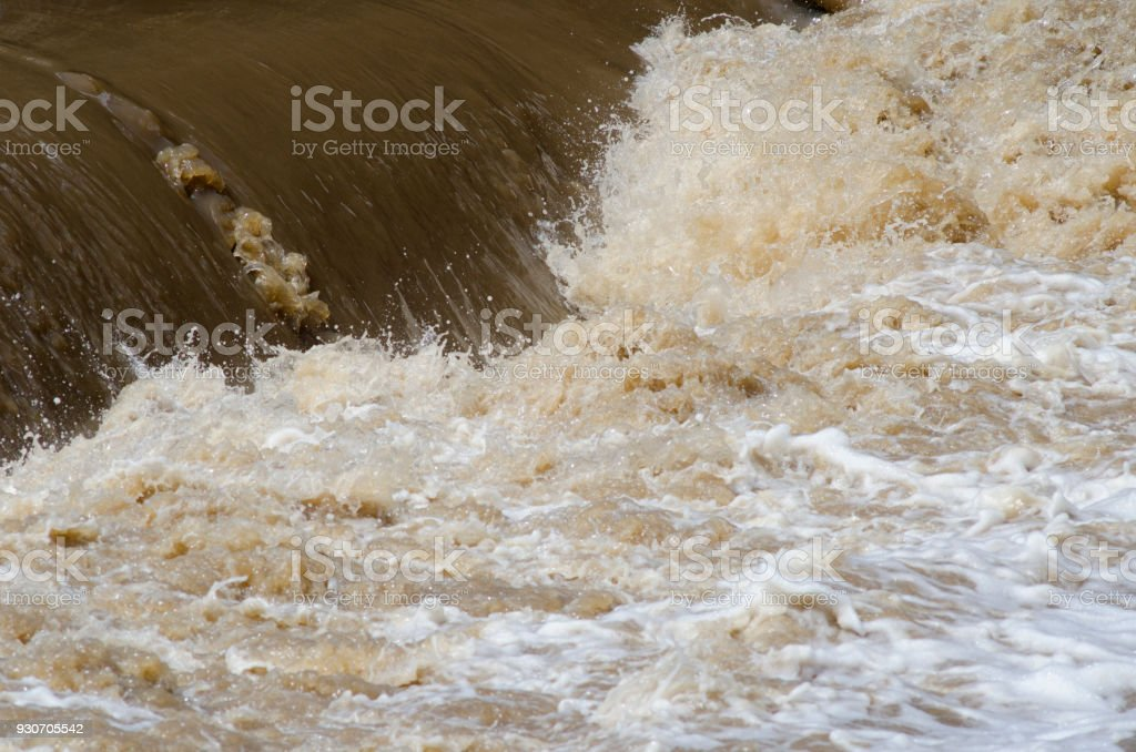 Turbid flood waters flow over a weir after heavy rains stock photo