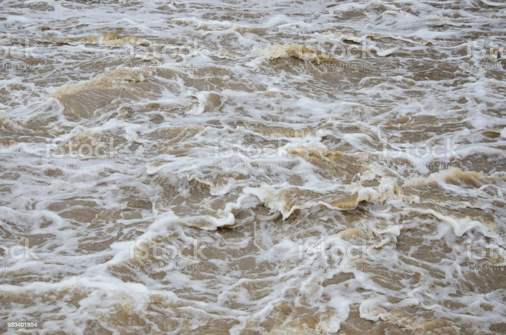 Turbid flood waters flow over rapids after heavy rains stock photo