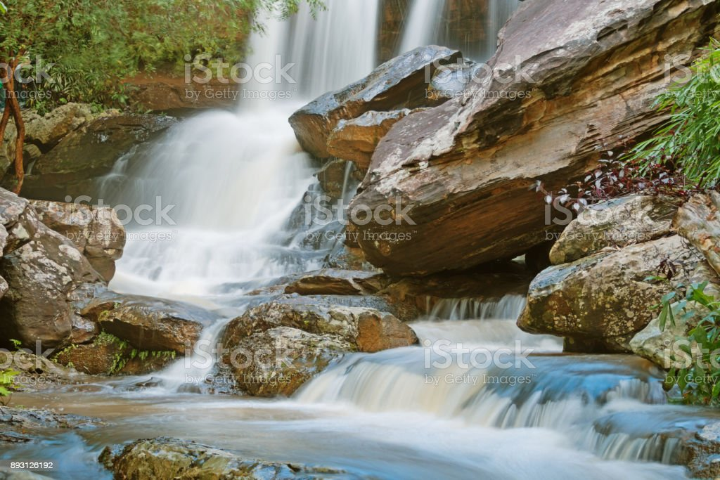 Turbid water at the waterfall with stone slide and danger stock photo