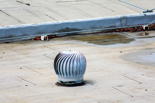 Weathered turbine vent on the flat roof in an industrial building. Ponding water on the settled flat roof.