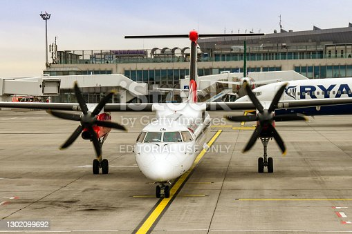 Budapest, Hungary - March 2019: Turboprop aircraft with engines running waiting to leave its stand at Budapest airport. One of the pilots is waving.
