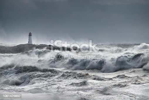 Waves break near the lighthouse at Peggy's Cove, Nova Scotia during a hurricane. Primary focus is on the water in the foreground.