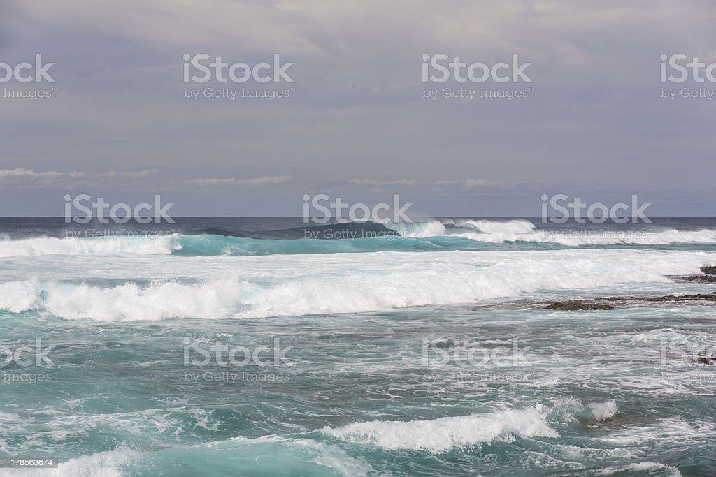 Turbulent ocean waves with white foam beat coastal stones royalty-free stock photo