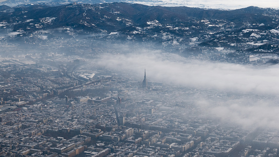 Turin aerial view. Torino cityscape from above, Italy. Winter, fog and clouds on the skylline. Smog and air pollution.