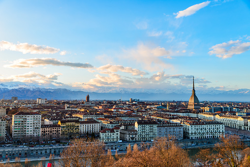 Turin skyline at sunset. Torino, Italy, panorama cityscape with the Mole Antonelliana over the city. Scenic colorful light and dramatic sky.