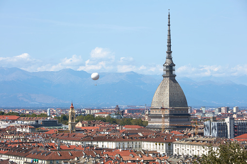Turin skyline view, Mole Antonelliana tower and hot air balloon in a sunny summer day in Italy