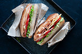 baget sandwich including turkey chese tomatoes and lettuce