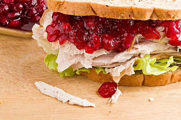 Turkey And Cranberry Sandwich A close up of a turkey and cranberry sandwich sitting on a wooden cutting board with a small brown bowl of homemade cranberry sauce in the background. leftovers stock pictures, royalty-free photos & images