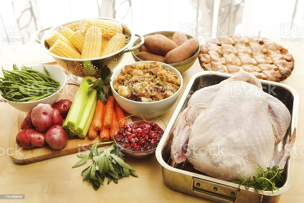 Turkey and Raw Ingredients for Thanksgiving Dinner Preparation Horizontal Fresh, uncooked ingredients for a Thanksgiving meal, including turkey, stuffing, corn, green beans, potatoes, yams, carrots, celery, cranberries, and herbs, and a cooked pie with lattice woven crust. American Culture Stock Photo