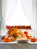 A Thanksgiving turkey sits ready to be carved for a Thanksgiving Day feast on a festively decorated dining room table.  The side items include pumpkin pie, stuffing, and steamed vegetables. Light streams in through a window in the background adorned with an autumn leaf garland.