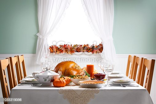 A Thanksgiving turkey sits ready to be carved for a Thanksgiving Day feast on a festively decorated dining room table.  The side items include pumpkin pie, stuffing, steamed vegetables, and cranberry sauce. Light streams in through a window in the background adorned with an autumn leaf garland.