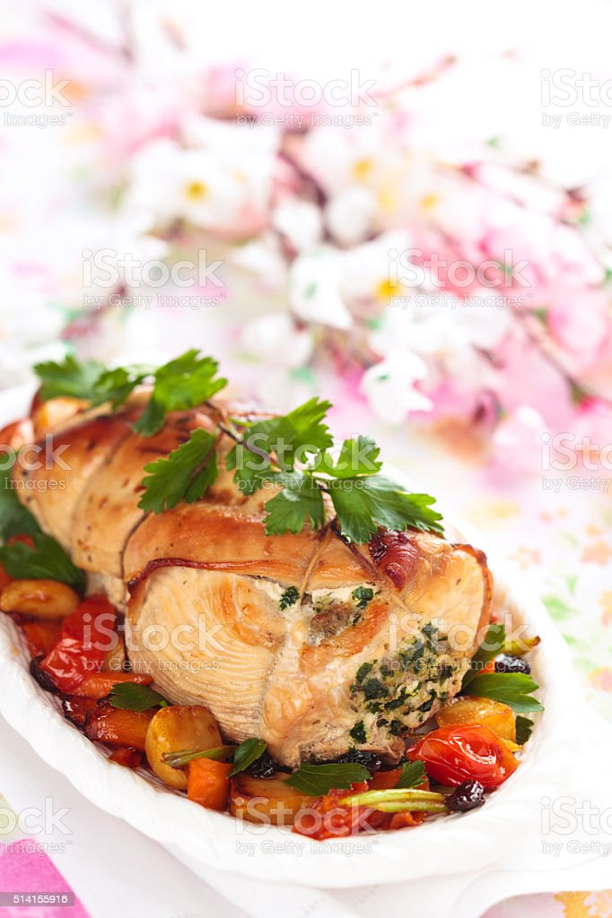 Border of stuffed turkey breast with baked vegetables, parsley and...