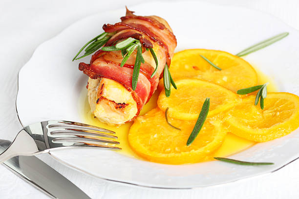 Turkey breast rolls (roulades) in bacon with orange sauce stock photo