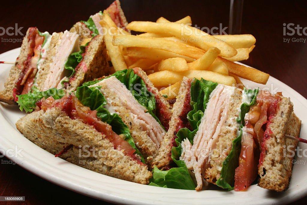 Turkey club sandwich and fries stock photo