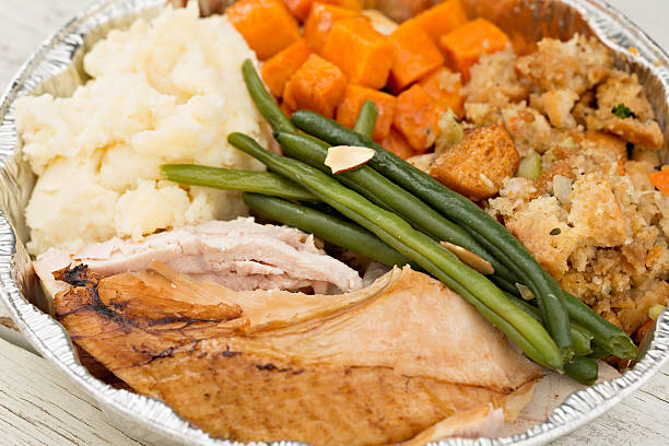 Turkey Dinner Leftovers A high angle close up shot of some Thanksgiving Day dinner leftovers placed in a pie sized aluminum container, they will be frozen and consumed at a later date. leftovers stock pictures, royalty-free photos & images