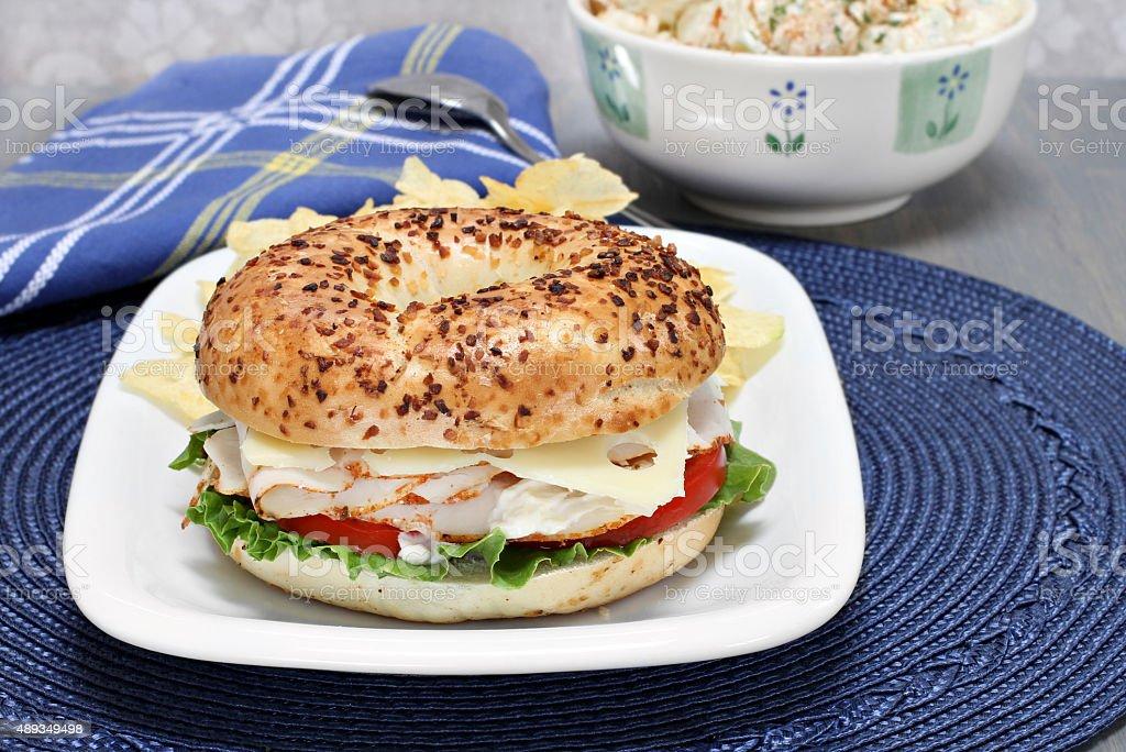 Turkey, lettuce, tomato, swiss cheese sandwich  on an onion bagel. stock photo