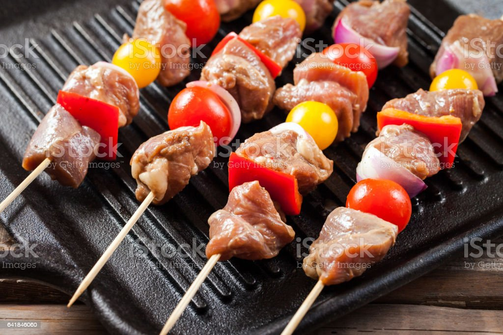 Raw turkey meat skewers with cherry tomatoes, pepper and onion on...