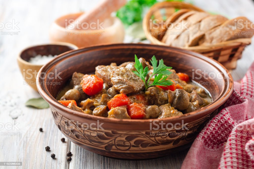 Turkey meat stew with mushrooms and vegetables in ceramic bowl on...