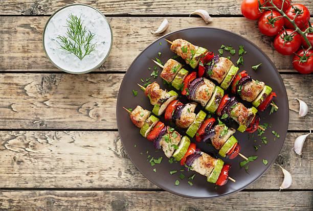 Turkey or chicken meat shish kebab skewers with chopped parsley Turkey or chicken meat shish kebab skewers with tzatziki sauce, chopped parsley, garlic and tomatoes on rustic wooden table background. Traditional barbecue grill food spit roasted stock pictures, royalty-free photos & images