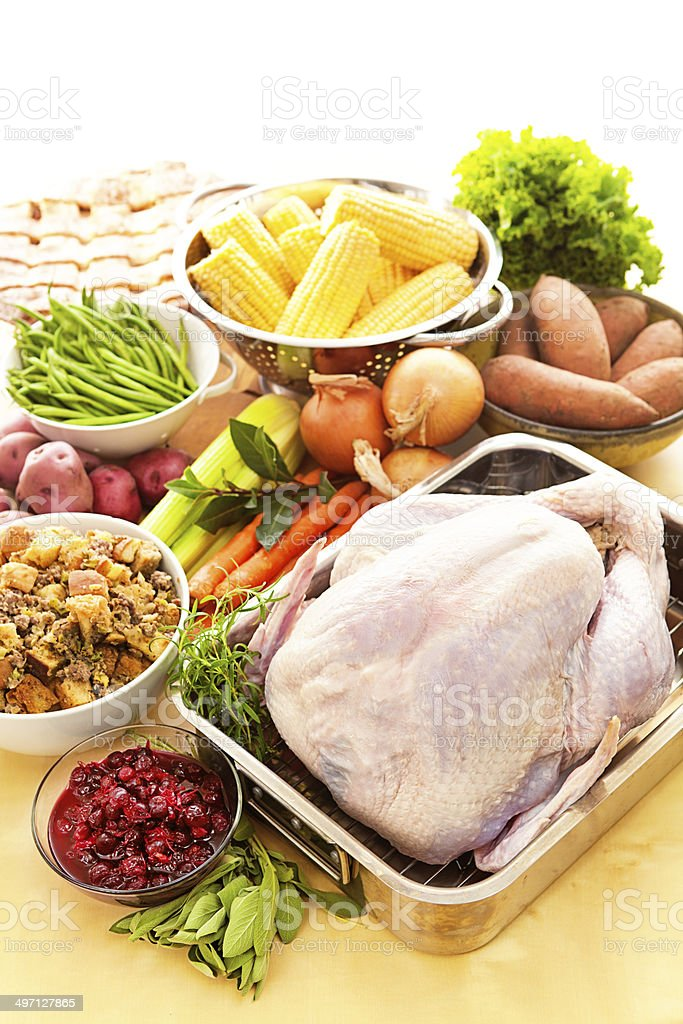 Turkey & Raw Ingredients for Thanksgiving Dinner Preparation Vertical Subject: Preparing a Thanksgiving dinner with turkey and all the accompaniments such as cranberry sauce, stuffing, sweet potatoes, corn, green beans, fresh herb and vegetable and apples pie. Abundance Stock Photo
