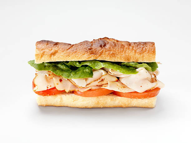Turkey Sandwich on a Baguette Turkey Sandwich on a Baguette with Lettuce and Tomato -Photographed on Hasselblad H3D2-39mb Camera submarine sandwich stock pictures, royalty-free photos & images