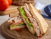 Healthy sandwich with turkey, tomato and lettuce on whole wheat bread on a wooden board