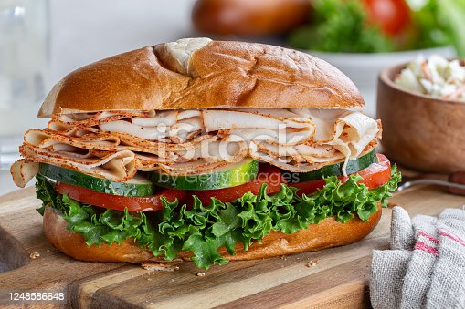 Turkey submarine sandwich with cucumber. tomato and lettuce on a wooden cutting board