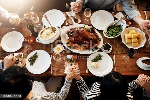 High angle shot of an unrecognizable family saying grace at the dining table on Thanksgiving