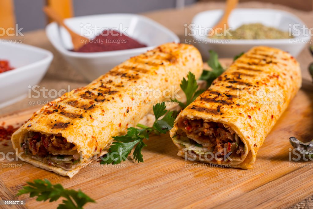 Turkish Adana wrap kebap on wood with appetizer stock photo