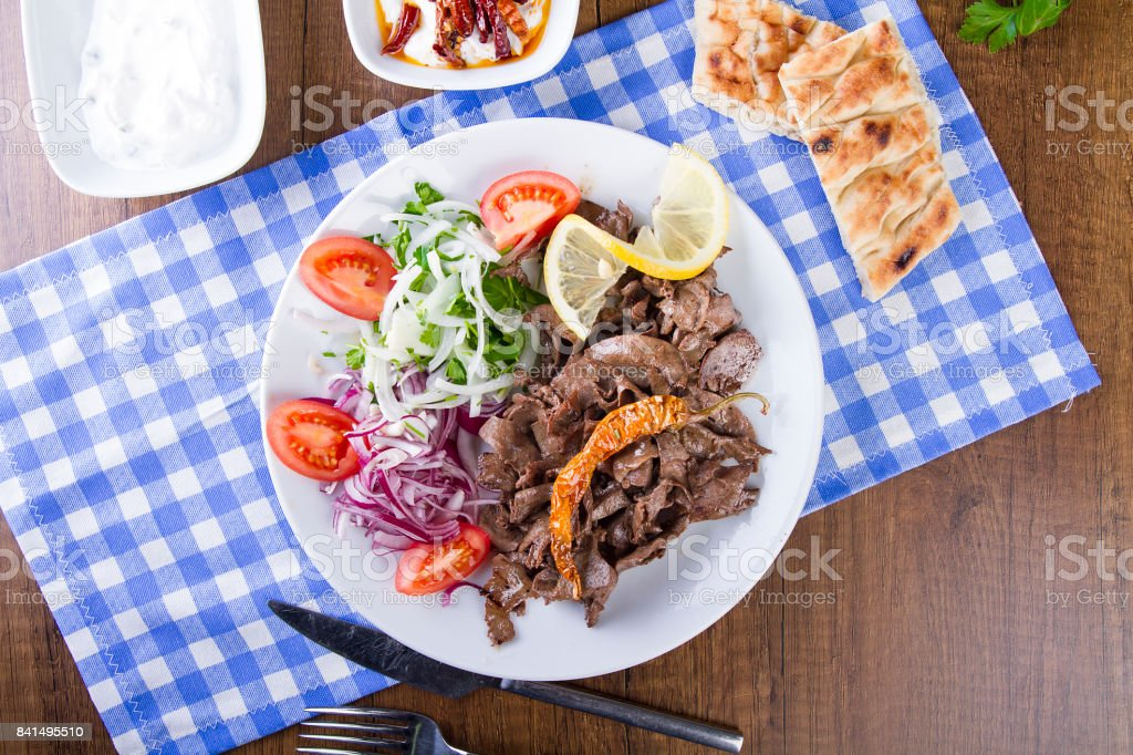 Turkish and Arabic Traditional Liver Doner Kebab serving witt salad, yogurt, lettuce, pita bread, onion, tomato and rice pilav in white plate on garnish restaurant background stock photo